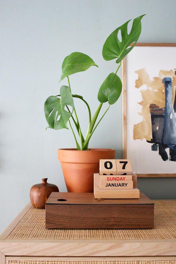 Rotan IKEA Stockholm kast met opbergdoos en een houten blokken kalender van House Doctor.
