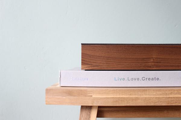 Skogsta bankje met houten opbergdoos CubiWood tegen een groene muur.