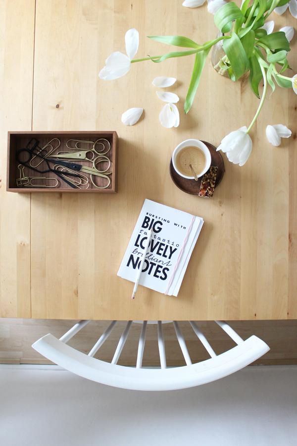 Witte spijlenstoel aan een houten eettafel met kop koffie en opbergdoos gevuld met scharen.