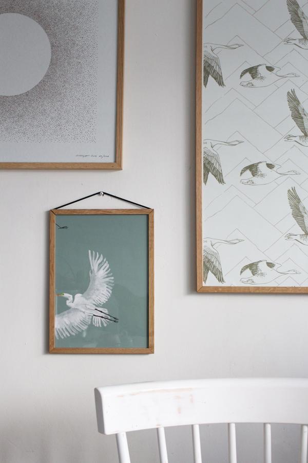 Witte muur met prints en ingelijst behang in licht houten lijsten - via Accessorize your Home
