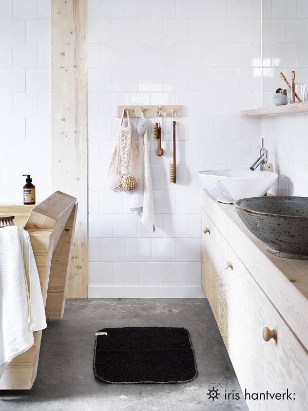 Lichte badkamer met houten kastjes en een rek vol handgemaakte borstels - via Accessorize your Home