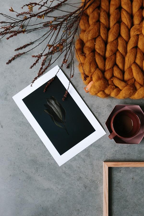 Flat lay van fotokunst van het Zweedse Kolla met burgundy koffiekopje en okergeel plaid - via Accessorize your Home