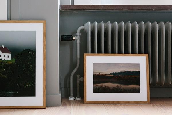 Fotokunst van het Zweedse Kolla in lichthoutenlijsten tegen grijze verwarming geplaatst - via Accessorize your Home
