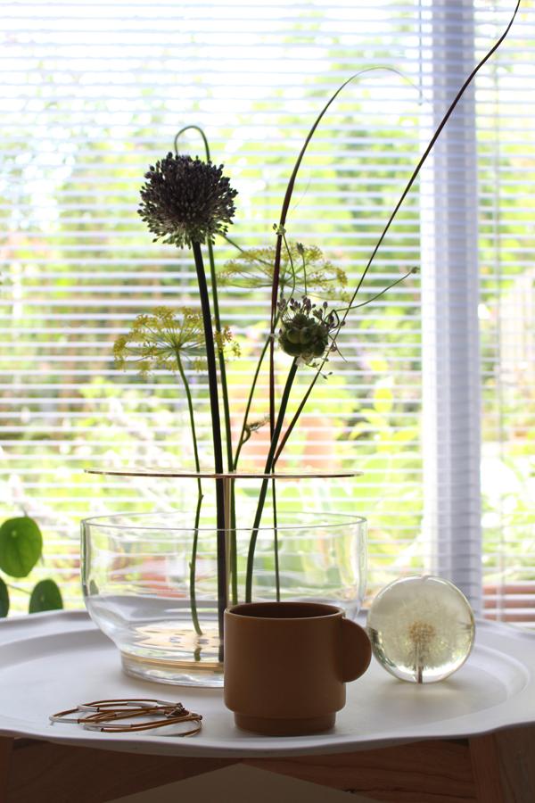 Ikebana vaas op wit metalen dienblad met presse papier met een paardenbloem en okergeel kopje - via Accessorize your Home