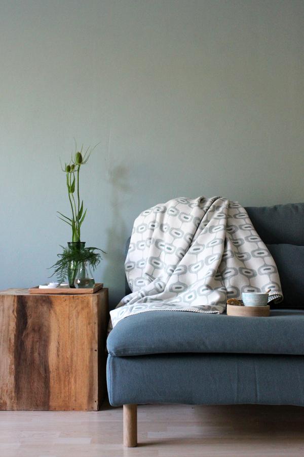 Plaid Doris van Klippan op Soderhamn bank van IKEA tegen grijsgroene muur - via Accessorize your Home
