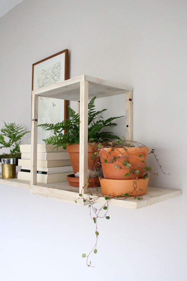 DIY zwevende wandplank met terracotta potten met planten en stapel boeken - via Accessorize your Home