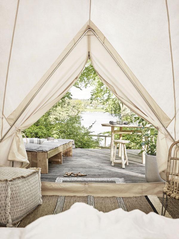 Vanuit de joert kijken op het terras met teakhouten meubels naar een met zon overgoten meertje